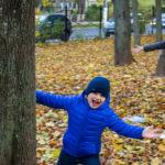 Мальчик радостно выпрыгивает из-за дерева в осеннем парке