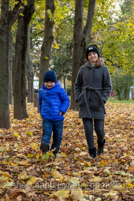 Мальчик и девочка подбрасывать желтые листья ногами в парке осенью - Украина, Одесса, 17,10,2019