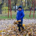 Мальчик в осеннем парке подбрасывает листья с ноги