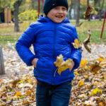 Мальчик в синей куртке улыбается и бросает желтые листья ногами в парке осенью