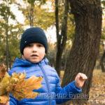 Мальчик с букетом желтых листьев в осеннем парке