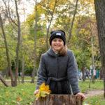 Девушка в сером пальто и черной шляпе в осеннем парке