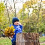 Мальчик откидывается на пене в осеннем парке