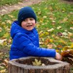 Мальчик играет в синей фуражке с листьями в осеннем парке