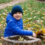 Мальчик играет возле срубленного дерева в осеннем парке