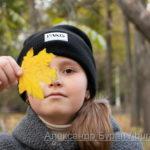 Девушка с желтый осенний лист рядом с ее лицом