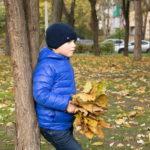 Мальчик с букетом желтых листьев стоит под деревом осенью в парке