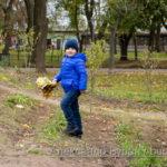 Мальчик в синей куртке поднимается на холм в осеннем парке