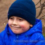 Улыбка мальчик с красными щечками в осеннем парке