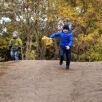 Маленький мальчик спускается с горки в осеннем парке