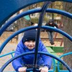 Мальчик в синей куртке лезет на горку кататься на металлические трубы