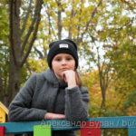 Девочка-подросток смотрит в камеру, стоя на деревянной площадке в парке осенью - Украина, Одесса, 17,10,2019