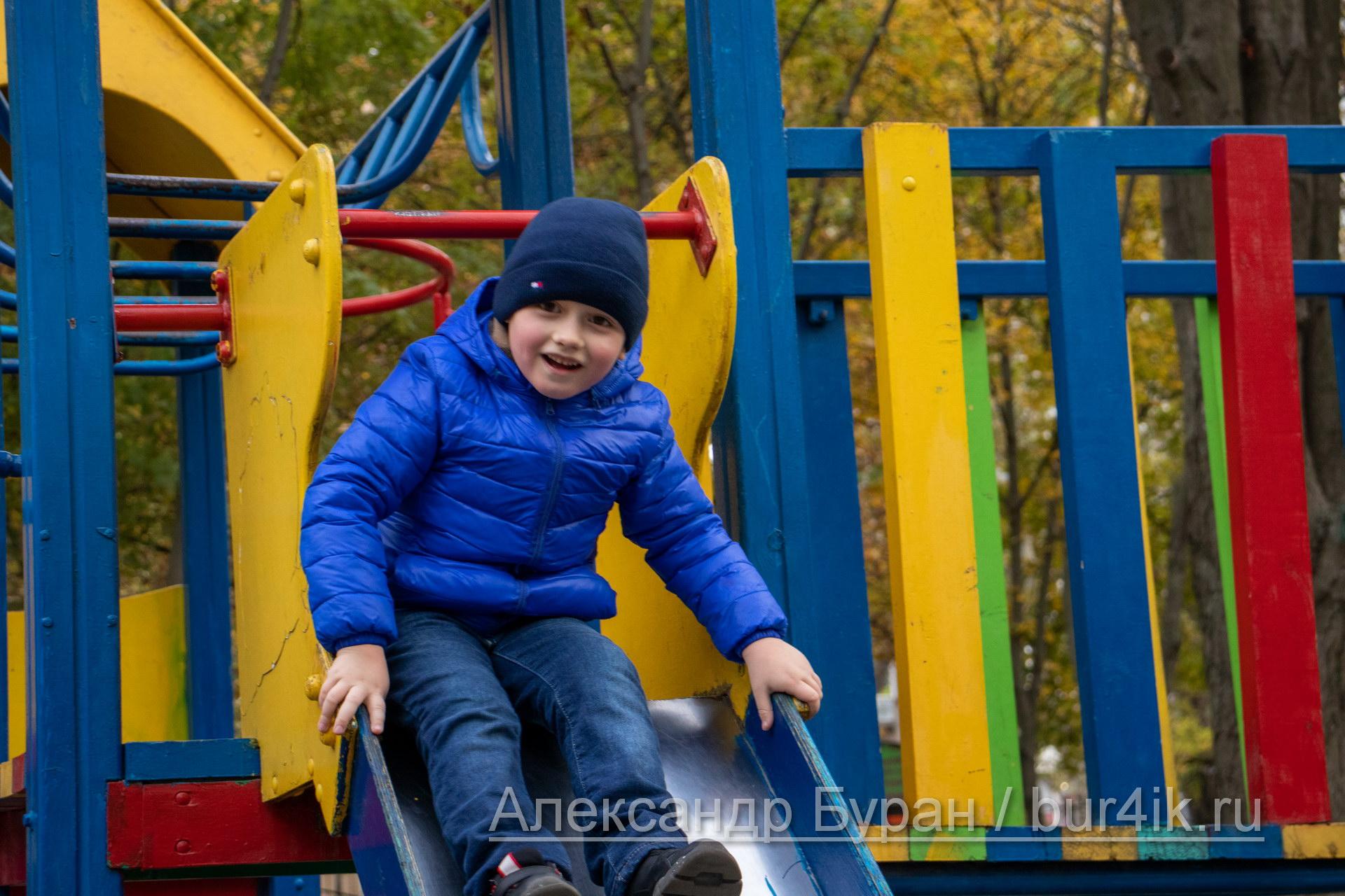 Мальчик в синей куртке катается на детской горкой в осеннем парке