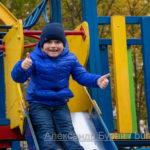 Мальчик едет вниз по склону холма в парке осенью