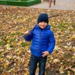 Мальчик в осеннем парке играет с сухой палкой из дерева