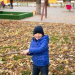 Мальчик с веткой дерева в руках в осеннем парке