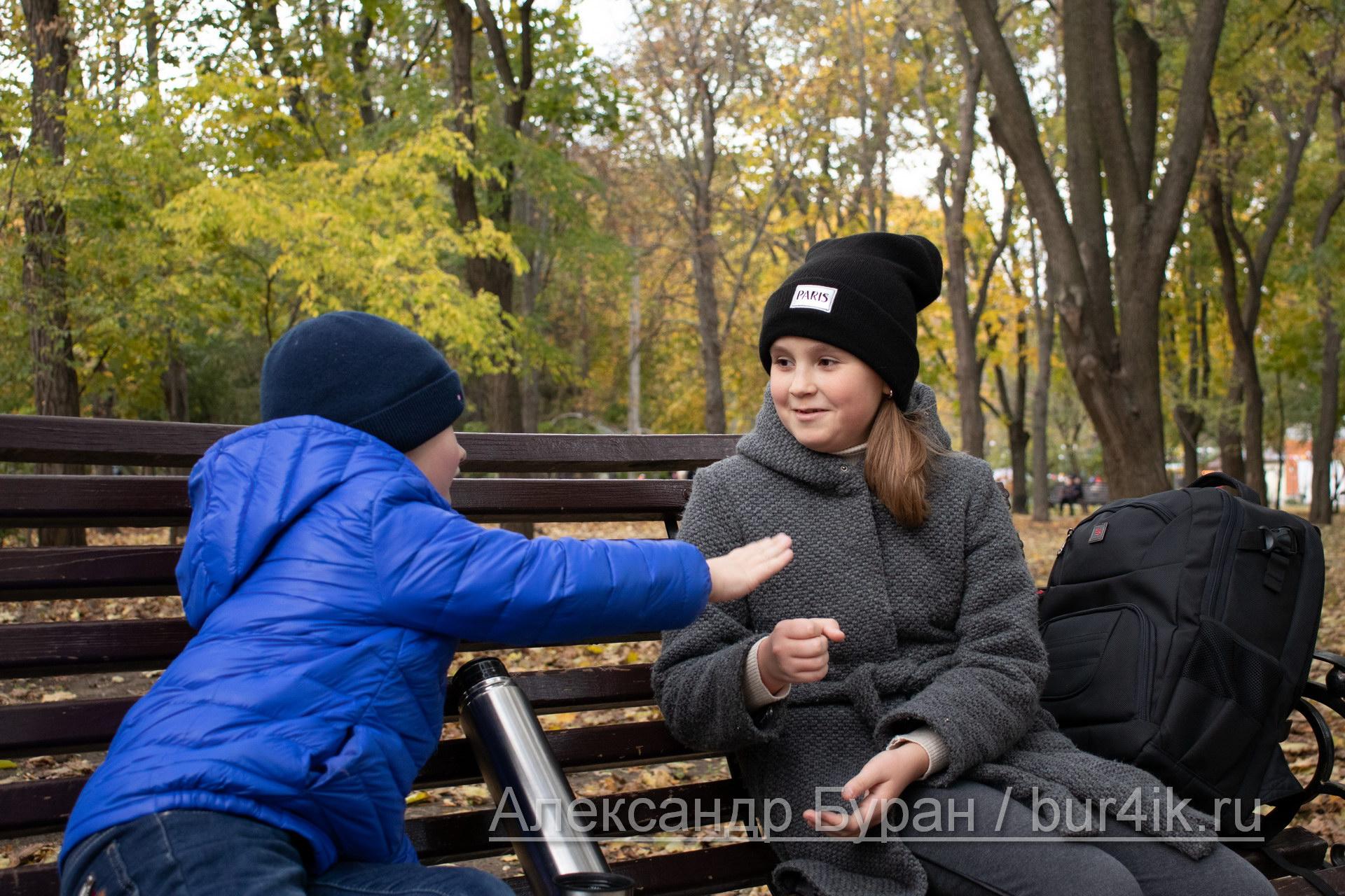 Девочка и мальчик сидят на скамейке поиграть в осеннем парке - Украина, Одесса, 17,10,2019
