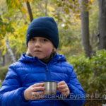 Мальчик пьет чай из термоса осенью в парке