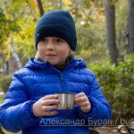Мальчик в парке осенью пьет чай из крышки термоса