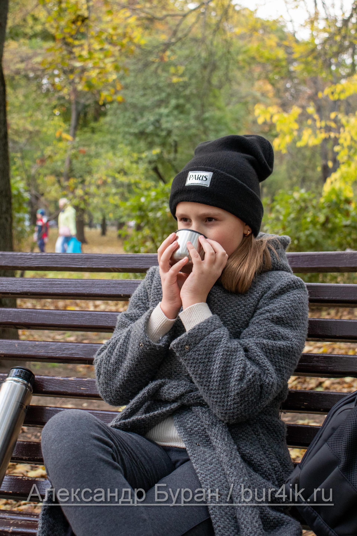 Девушка в парке пьет чай из крышки термоса в осенне - Украина, Одесса, 17,10,2019