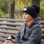 Девочка пьет теплый чай из термоса в парке осенью
