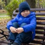 Мальчик в парке сидит на скамейке, подняв ее ноги