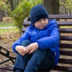 Мальчик в парке залезла на скамейку с ногами