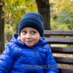 Портрет улыбающегося мальчика, который сидит на скамейке в парке осенью