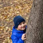 Мальчик прячется за деревом в осеннем парке