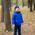 Маленький мальчик стоит на старом дереве и howslike как волк в парке осенью