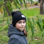 Девушка позирует в осеннем парке на фоне последней зеленой листвы