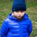 Мальчик в синей куртке выглядит оскорбленным в сторону