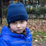 Мальчик в плохом настроении на прогулке в парке осенью