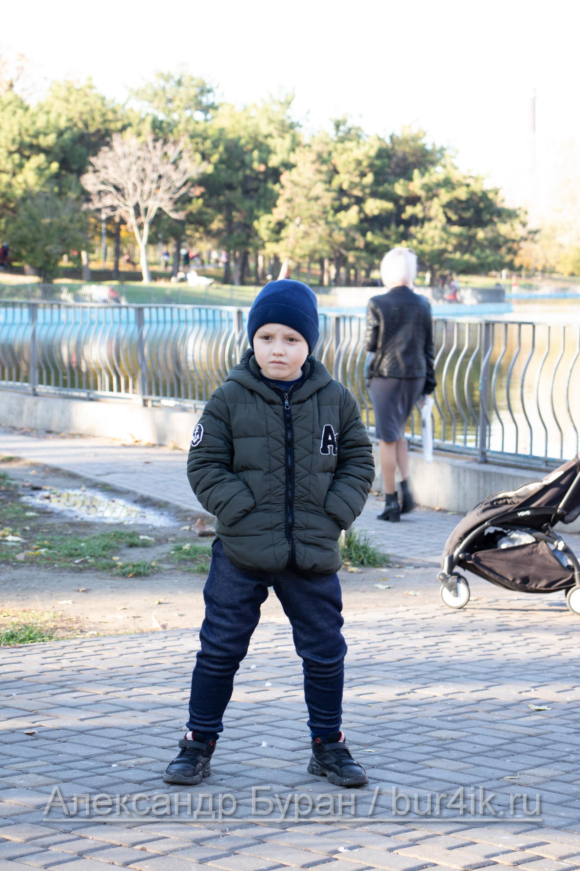Шесть-летний мальчик стоит у пруда в осеннем парке