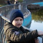 Мальчик на перила вокруг пруда в парке