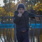 Мальчик на перила вокруг пруда в парке показывает большой палец