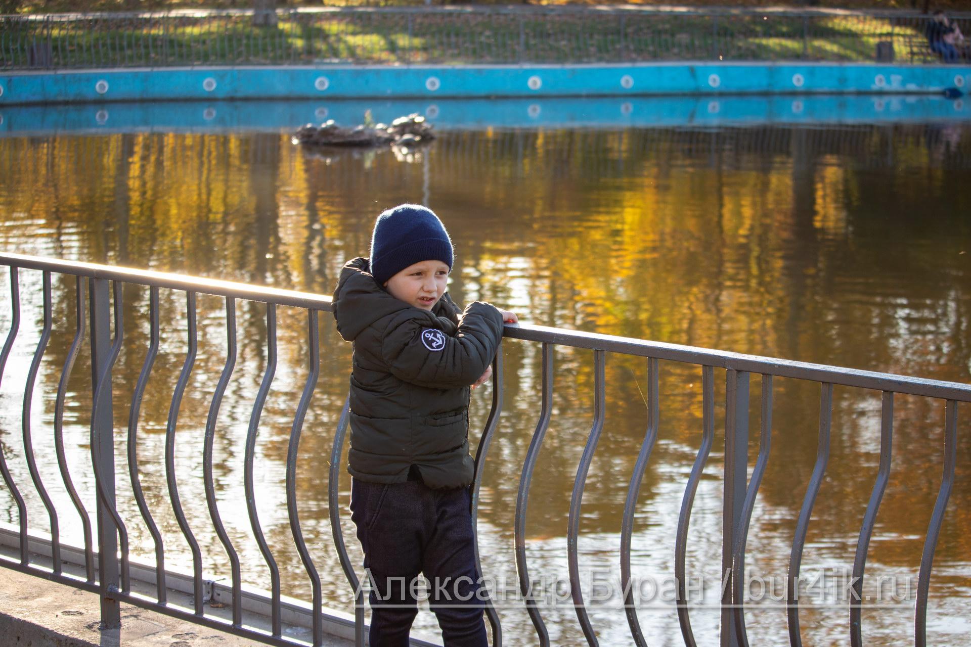 Мальчик ходит вокруг пруда в парке