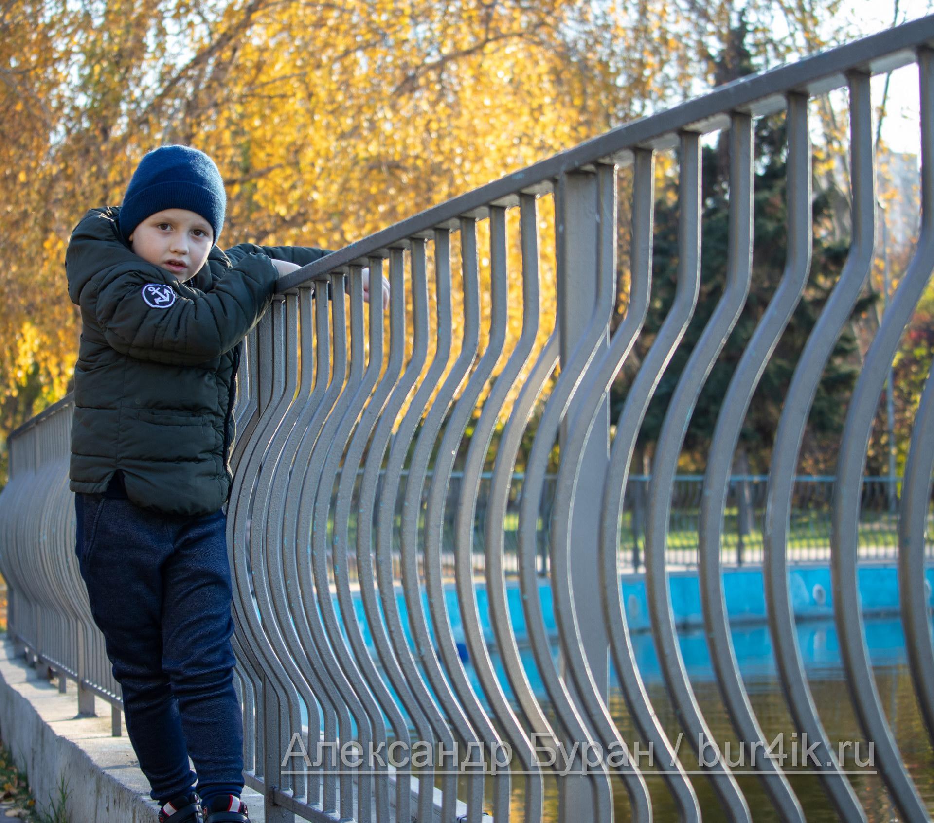 Мальчик ходит вдоль перил на берегу пруда в парке