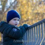 Мальчик держится за перила и смотрит на озеро в парке
