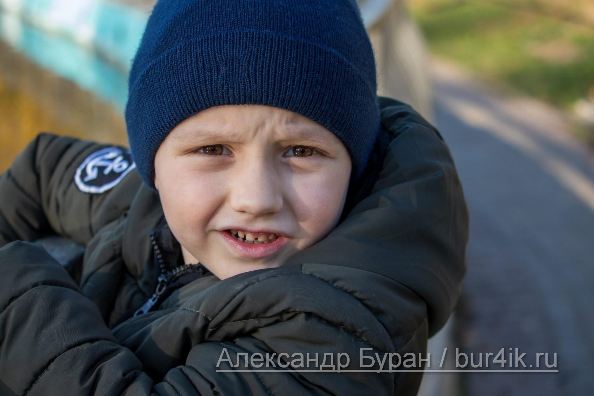 Мальчик в синей фуражке смотрит в камеру на прогулке в осеннем парке у пруда