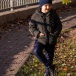 Мальчик фотографируется возле пруда в осеннем парке
