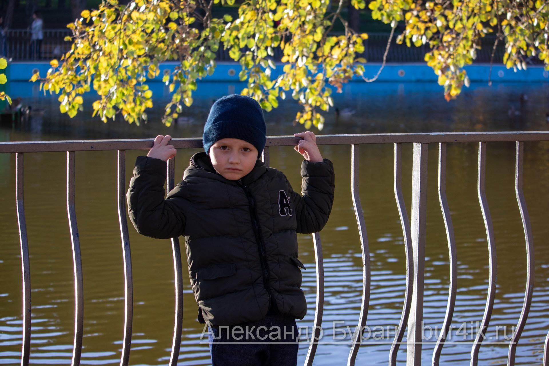 Мальчик спиной к озеру в парке
