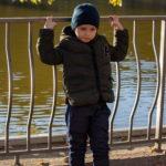 Мальчик спиной к озеру в парке и листва над головой