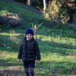Мальчик на слайде покрыта травой в парке