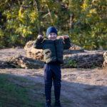 Мальчик в спортивных штанах и куртке на горе в парке