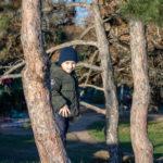 Мальчик в шляпе бежит вниз по холму в парк