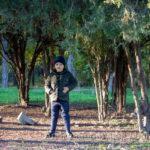 Мальчик среди хвойных деревьев в осеннем парке