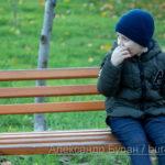 Мальчик ест яблоко на скамейке в осеннем парке