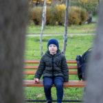 Мальчик на скамейке, на переднем плане деревья