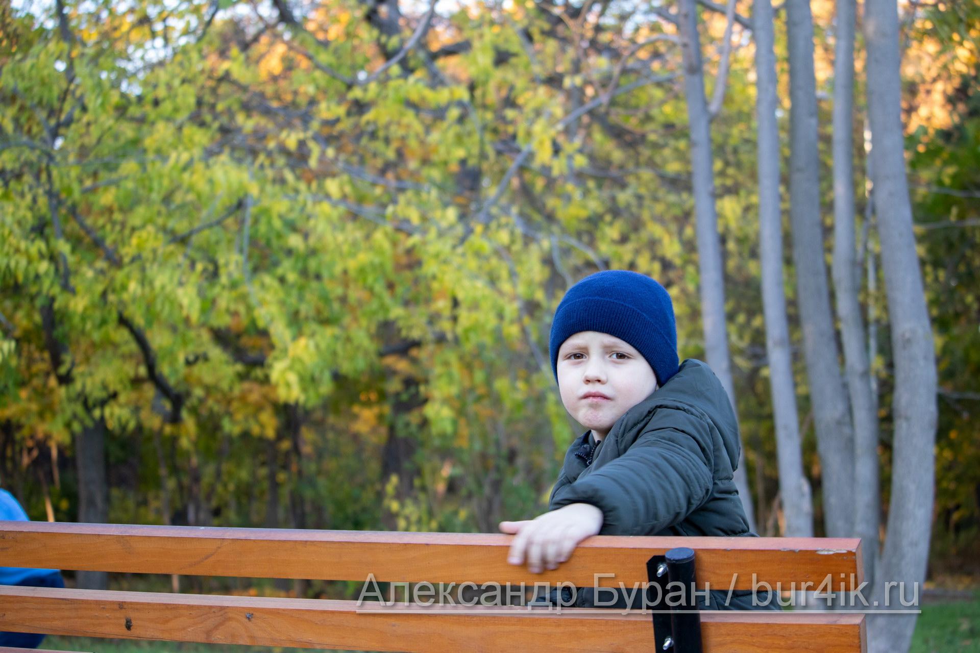 Мальчик сидит на скамейке в перерыве в осеннем парке
